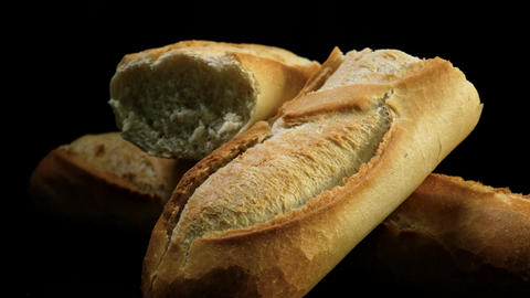 Freshly baked baguettes rotate against black background Footage