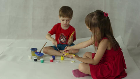 Children draw on paper with brushes, palms and gouache Footage