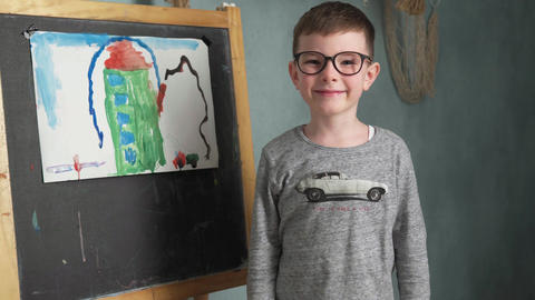 boy standing beside his drawing Footage