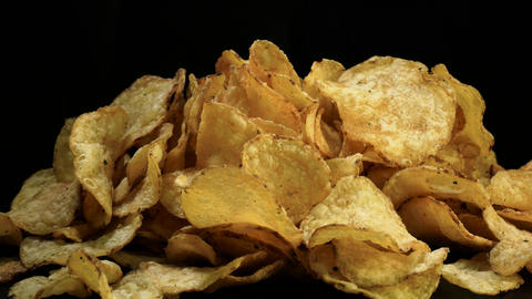 Salted potato chips rotate against black background Footage