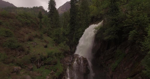 Powerful waterfall pours out into green hillside Footage