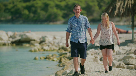 Couple Holding Hands and Walks on Shore Footage