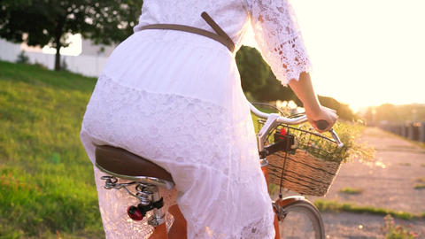 Young beautiful woman riding a bicycle at sunset Footage