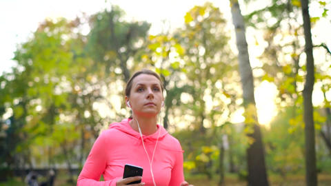 Close up of woman with headphones and smartphone running through an autumn park Footage