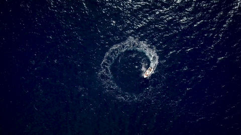 Aerial view of a motor boat designing a circle in the sea navigating fast Live Action
