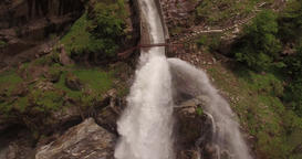 Powerful waterfall pours down a grassy and rocky cliff Footage