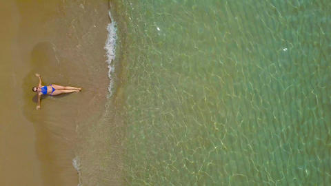Aerial shot of a woman in a bikini lying on a sandy beach and waves wash her Footage