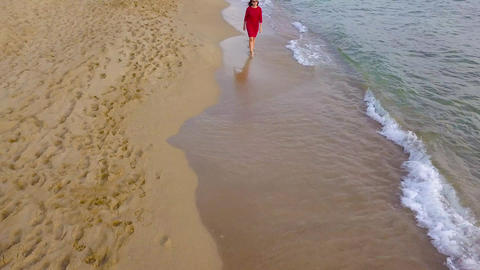 Top view of a woman walking barefoot along wet sand beach. Running wave is Footage