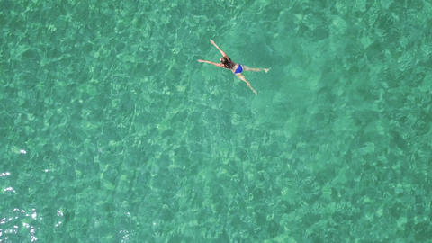 View from the height on swimming woman in the clear sea Footage