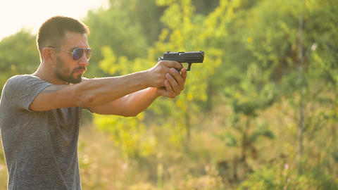 Young man is shooting from a gun, close up. Slow motion Footage