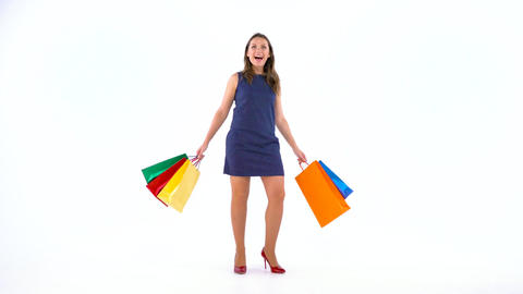 Female shopper holding multicolored shopping bags on white background in studio Footage