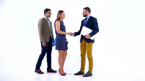 Group of three business partners shake hands welcoming each other in studio Footage