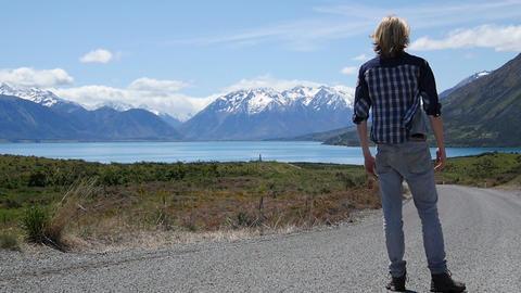 Man Walks Down Road Toward Mountains and Lake ビデオ