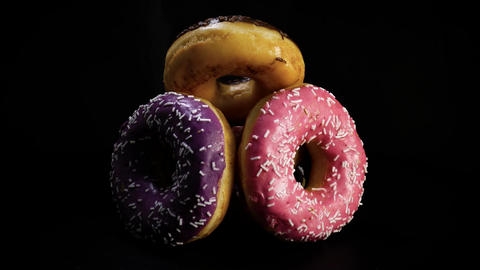 Sweet donuts rotate against black background Footage