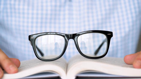 Man takes his glasses and reads a book close up ビデオ