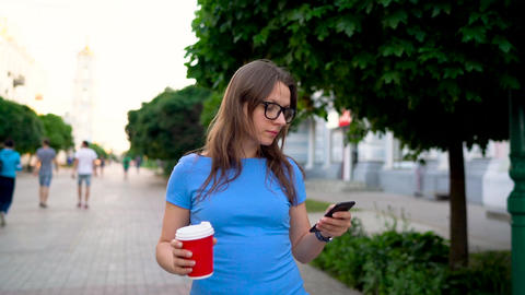 Woman talking on the smartphone and drinking coffee walking down the street Footage