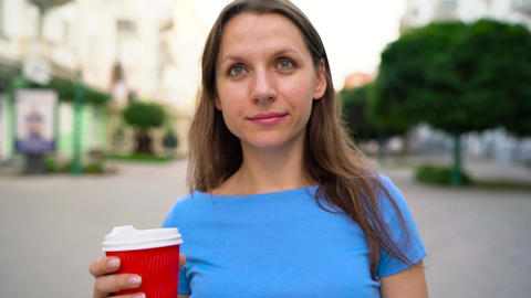 Happy woman drinking coffee on an urban street Footage