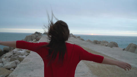Woman in red dress runs to the lighthouse on the ocean coast Footage