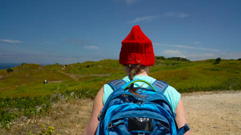 Woman with a backpack goes on a picturesque hilly terrain to the ocean Footage