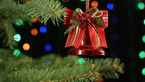 Christmas bell on the Christmas tree on dark background with garland Footage