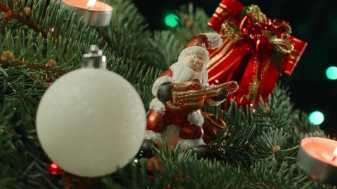 Christmas decoration with Santa, baubles and fairy lights on a dark background Footage