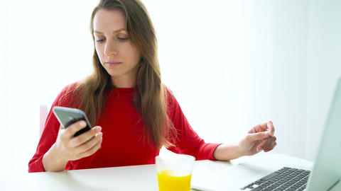 Smiling woman sitting at white home office and talking on smartphone Footage