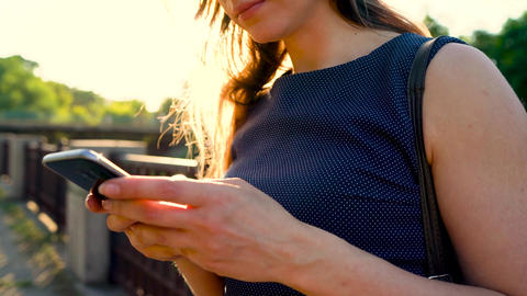 Woman in sunglasses using a smartphone outdoors at sunset Footage