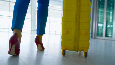 Woman in bright clothes is rolling yellow suitcase in the airport Footage