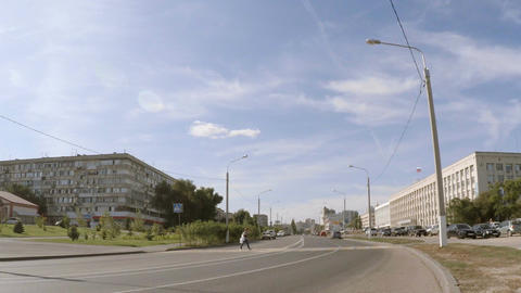 Cars pass a pedestrian on a city road Footage