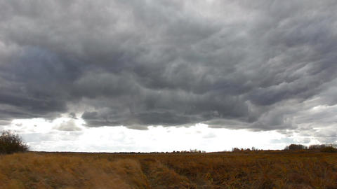 Dark storm clouds fly over the field Footage