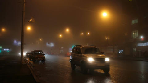The lights of night city in fog and cars on road Footage