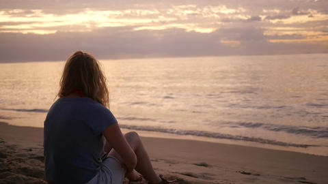 Woman Sits on Beach at Sunrise Footage