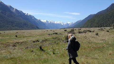 Woman Walks Through Field Between Mountains Footage