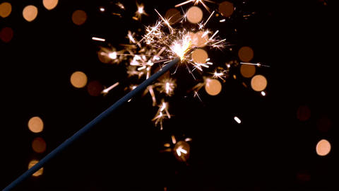 Sparkler burning in front of ambient lights in slow motion Footage