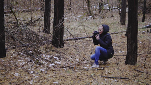 the girl shoots the autumn landscape in the forest. late autumn, the first snow Footage