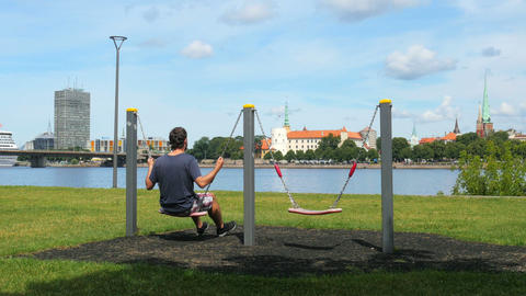 man swinging on swing, watching riga view, latvia Footage