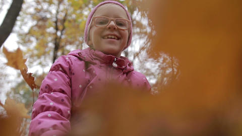 Smiling girl throwing maple leaves in autumn Footage