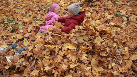 Playful kids lying in pile of yellow foliage Footage