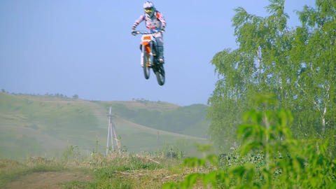 Racer jumping in to camera on motocross track aerial shot. Wide shot of in front Bild