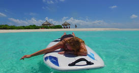 v11974 one 1 beautiful young girl in bikini sunbathing on surfboard paddleboard Footage