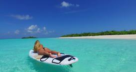 v11916 one 1 beautiful young girl in bikini sunbathing on surfboard paddleboard Footage