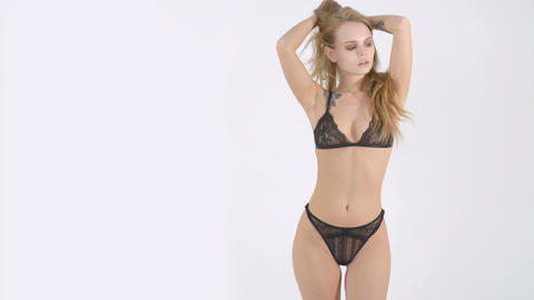 Beautiful woman in sexy black lingerie posing on a white background Footage
