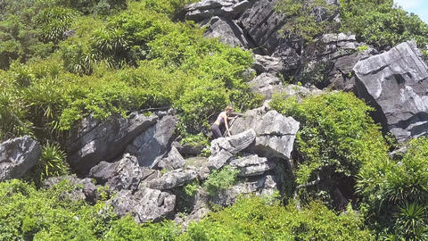Drone Removes from Girl Climbing up Large Sharp Rocks Footage