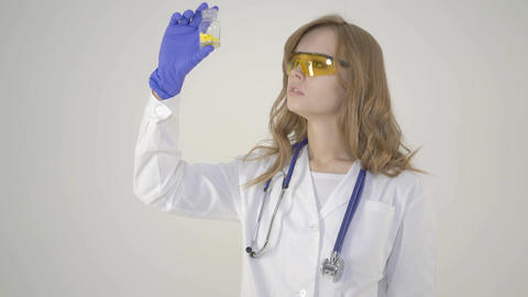 young nurse - beautiful woman medical worker holding jar of pills on white Footage