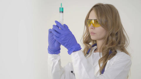 Young woman doctor holding syringe on white background Footage