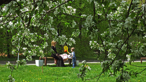 Young woman with a child playing in a spring park Footage