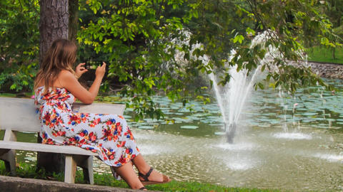 Blond Girl Sits on Bench at Fountain Takes Photos with Iphone Footage