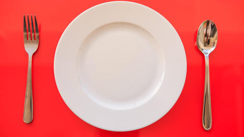 Hands Put Fork Spoon Vertically by Plate on Red Table Footage
