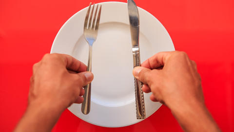 Hands Put Fork Knife Vertically on Plate on Red Table Footage