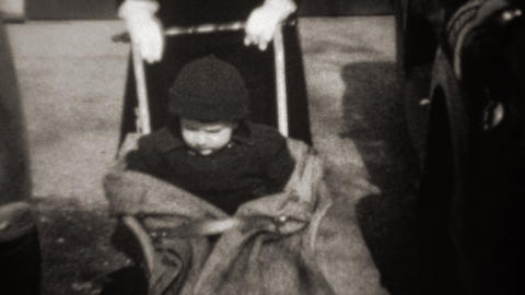 1941: Mother pushing baby stroller wearing black funny tiny fashion hat Footage